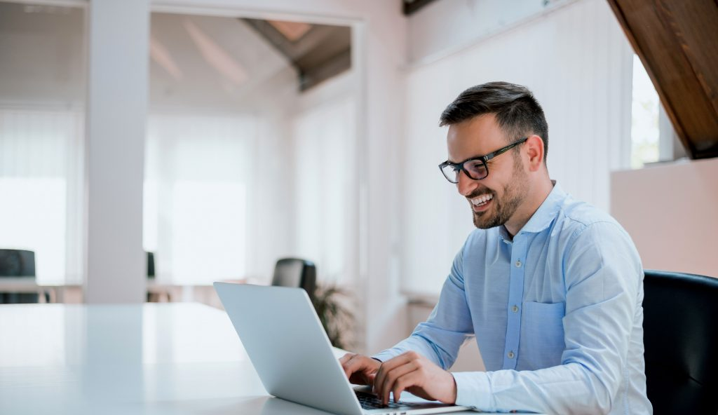 business man with glasses sitting at computer