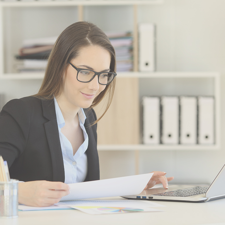 business woman at computer with reports